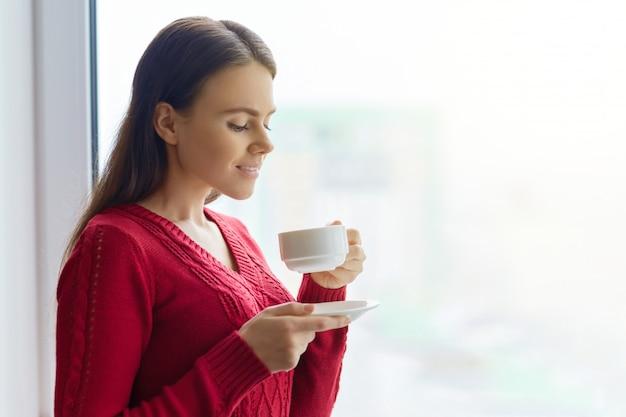 Młoda uśmiechnięta kobieta cieszy się aromatyczną kawę