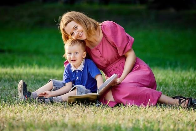 Młoda uśmiechnięta kobieta czyta książkę chłopcu siedzącemu na trawie w parku