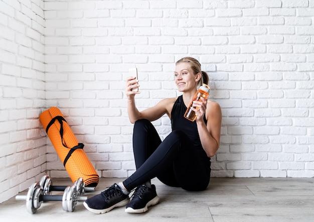 Młoda uśmiechnięta kobieta fitness robi selfie po treningu, siedząc na podłodze wody pitnej