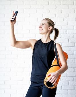 Młoda uśmiechnięta kobieta fitness robi selfie po treningu