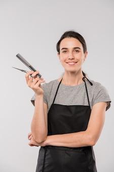 Młoda uśmiechnięta kobieta fryzjerka trzymając szczotkę do włosów i nożyczki i patrzy na ciebie na białym tle