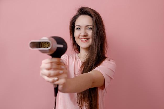 Młoda uśmiechnięta kobieta jak gangster z suszarką do włosów w ręce na różowym tle