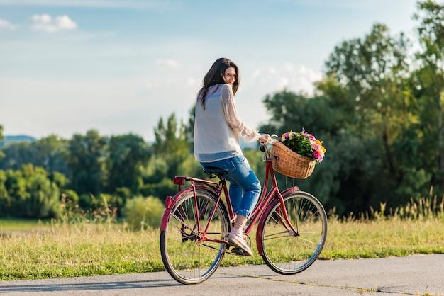 Młoda uśmiechnięta kobieta jedzie na rowerze z koszem pełnym kwiatów na wsi