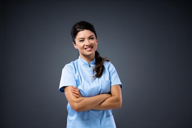 Młoda uśmiechnięta kobieta lekarz stojący z rękami skrzyżowanymi