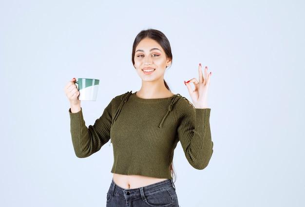 Młoda uśmiechnięta kobieta model trzyma kubek i pokazuje ok gest.