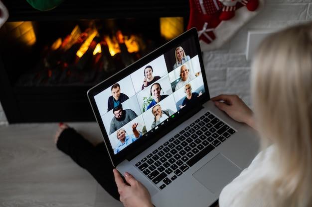 Młoda uśmiechnięta kobieta nawiązująca wideorozmowę w sieci społecznościowej z rodziną i przyjaciółmi w boże narodzenie.