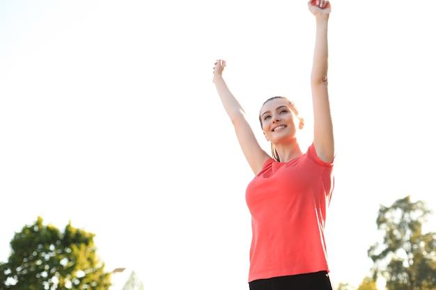 Młoda uśmiechnięta kobieta odpoczywa po aktywnym treningu fitness w parku.