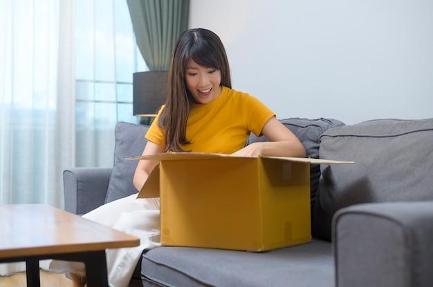 Młoda uśmiechnięta kobieta otwierająca kartonowe pudełko w salonie w domu