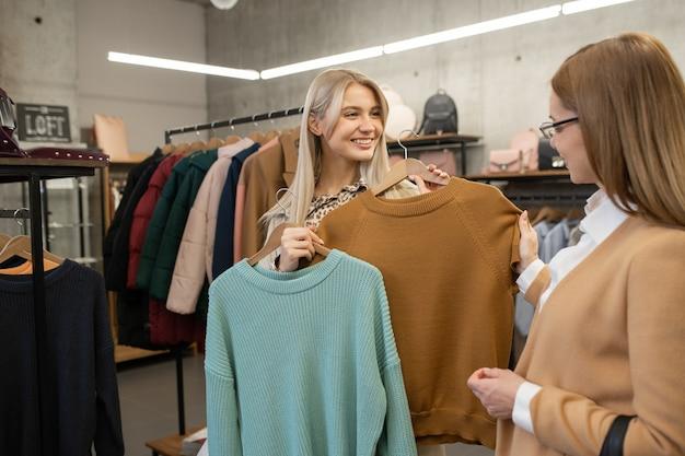 Młoda uśmiechnięta kobieta patrzy na matkę stojąc wśród regałów w butiku i konsultując się, jaki kolor swetra wybrać