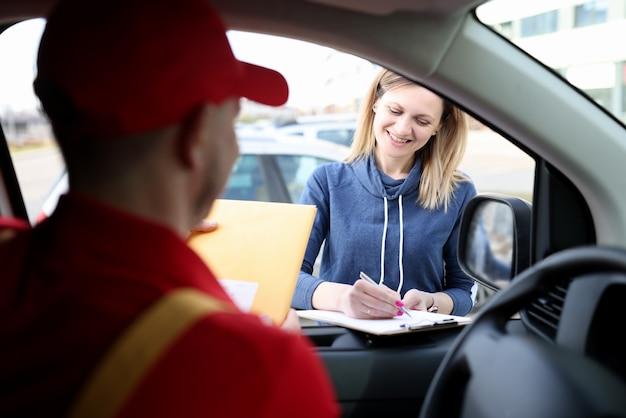 Młoda uśmiechnięta kobieta podpisująca pokwitowanie dostawy w pobliżu samochodu kurierskiego