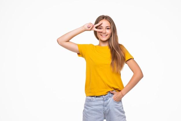 Młoda uśmiechnięta kobieta pokazuje znak zwycięstwa lub pokoju na białym tle na białej ścianie