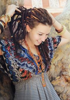 Młoda uśmiechnięta kobieta portret z dredami ubrana w ozdobną sukienkę w stylu boho