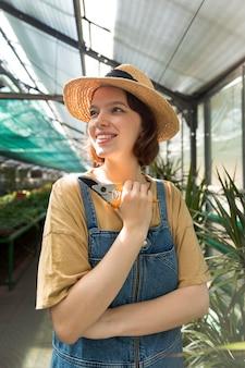 Młoda uśmiechnięta kobieta pracująca w szklarni