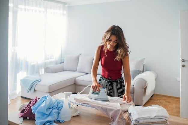 Młoda uśmiechnięta kobieta prasowania ubrania na deska do prasowania w domu
