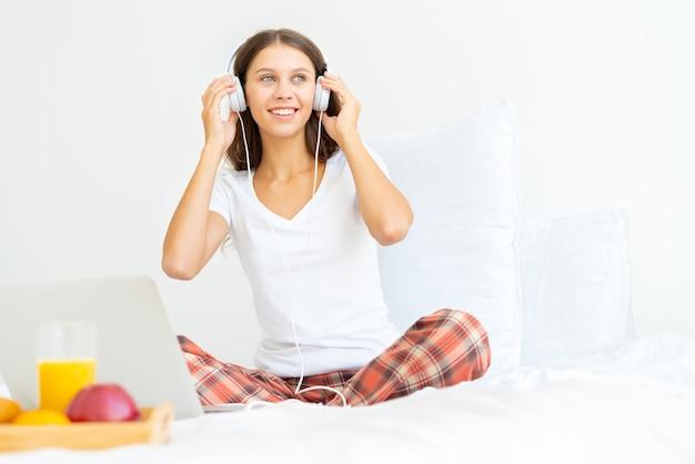 Młoda uśmiechnięta kobieta siedzi na łóżku w sypialni i słuchanie muzyki