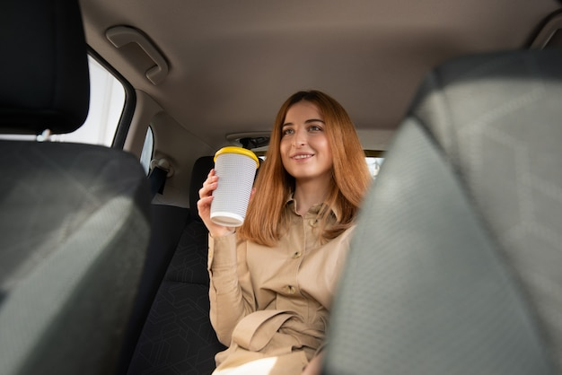 Młoda uśmiechnięta kobieta siedzi na tylnym siedzeniu pasażera i trzymając kubek gorącego napoju, czekając w korku