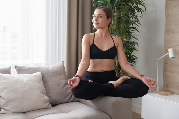 Młoda uśmiechnięta kobieta siedzi ze skrzyżowanymi nogami na kanapie w pozycji lotosu jogi, medytując w domu w życiu
