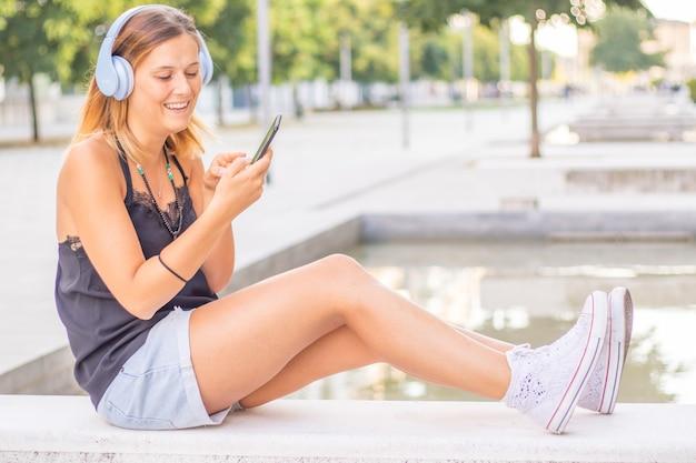 Młoda uśmiechnięta kobieta słucha muzyki przez słuchawki