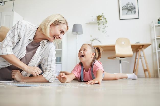 Młoda uśmiechnięta kobieta spędza czas z córką, śmiejąc się leżąc na podłodze i zbierając puzzle w domu