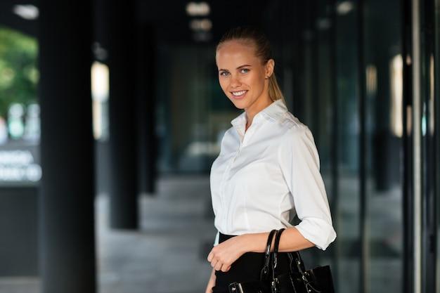 Młoda uśmiechnięta kobieta stojąca i trzymająca torebkę na zewnątrz