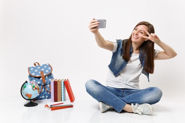 Młoda uśmiechnięta kobieta studentka robi selfie strzał na telefon komórkowy pokazując znak zwycięstwa w pobliżu kuli ziemskiej, plecaka, podręczników szkolnych na białym tle na białej ścianie