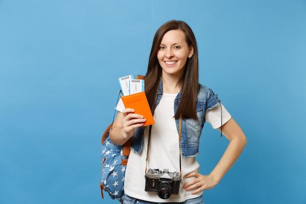Młoda uśmiechnięta kobieta studentka z plecakiem i retro vintage aparat fotograficzny na szyi, trzymając bilety na pokład paszportu na białym tle na niebieskim tle. kształcenie na uniwersytecie za granicą. lot w podróży lotniczej.