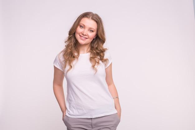 Młoda uśmiechnięta kobieta stwarzających nad białą ścianą z miejsca na kopię