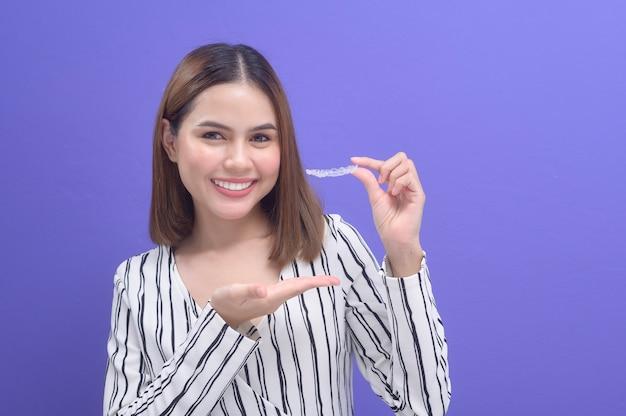 Młoda uśmiechnięta kobieta trzyma aparat ortodontyczny invisalign w studiu, opieki stomatologicznej i koncepcji ortodontycznej