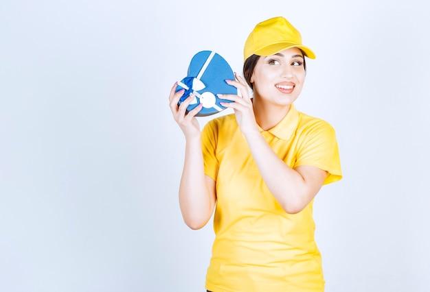 Młoda uśmiechnięta kobieta trzyma pudełko i zastanawia się, co jest w środku