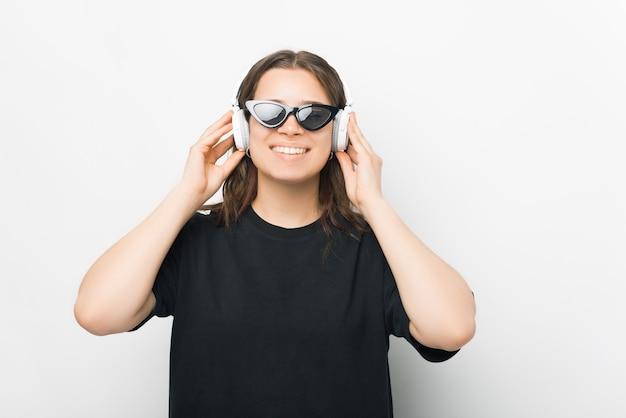 Młoda uśmiechnięta kobieta trzyma słuchawki i słucha muzyki, książki audio lub medytacji.