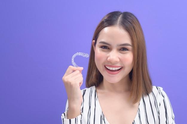 Młoda uśmiechnięta kobieta trzyma szelki invisalign w studio, opieki stomatologicznej i koncepcji ortodontycznej.