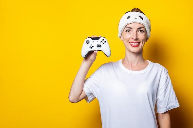 Młoda uśmiechnięta kobieta trzyma w ręce joystick.