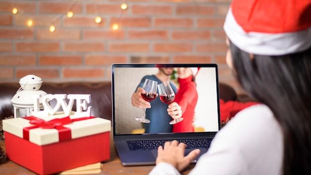 Młoda uśmiechnięta kobieta ubrana w czerwony kapelusz świętego mikołaja, nawiązywanie połączenia wideo w sieci społecznościowej z rodziną i przyjaciółmi w boże narodzenie.