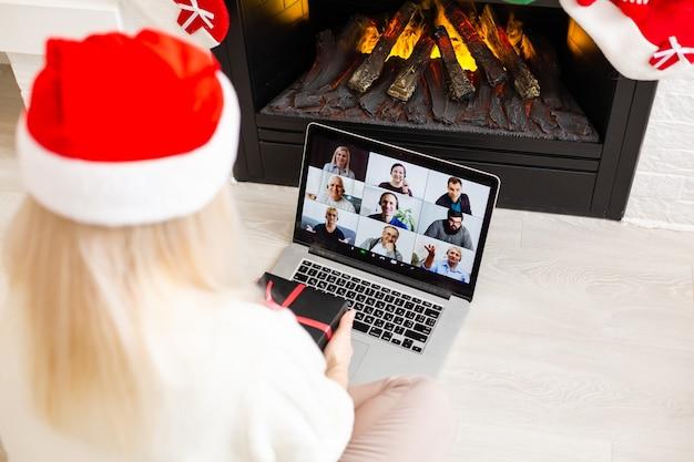 Młoda uśmiechnięta kobieta ubrana w czerwony kapelusz świętego mikołaja podczas rozmowy wideo w sieci społecznościowej z rodziną i przyjaciółmi w boże narodzenie.