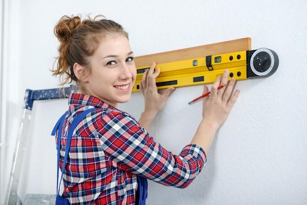 Młoda uśmiechnięta kobieta używa spirytusowego poziom