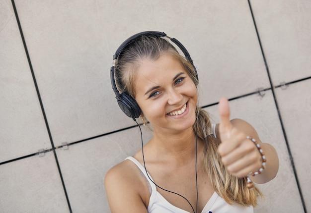 Młoda uśmiechnięta kobieta w białej koszulce z słuchaniem muzyki i pokazuje kciuk do góry
