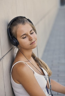 Młoda uśmiechnięta kobieta w białej koszulce z słuchaniem muzyki i siedząc na chodniku