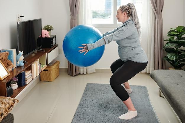 Młoda uśmiechnięta kobieta w ciąży robi przysiady z piłką fitness w dłoniach