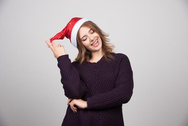 Młoda uśmiechnięta kobieta w kapeluszu santa stoi i pozuje.