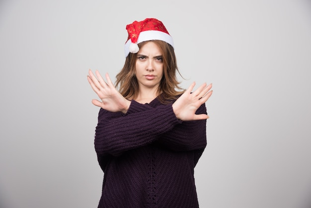 Młoda uśmiechnięta kobieta w kapeluszu świętego mikołaja pokazując znak stop z rękami.