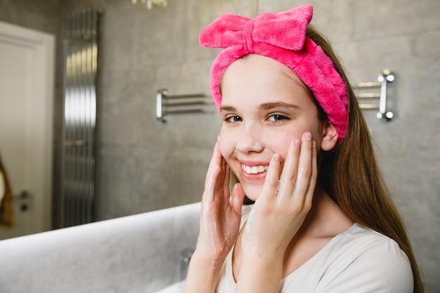 Młoda uśmiechnięta kobieta w kokardce z różowymi włosami usuwa makijaż i myje skórę w łazience, higieniczny rytuał domowy, pieniące dłonie i policzki