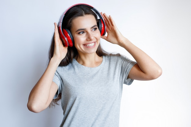 Młoda uśmiechnięta kobieta w nowoczesnych słuchawkach słucha muzyki na białym tle