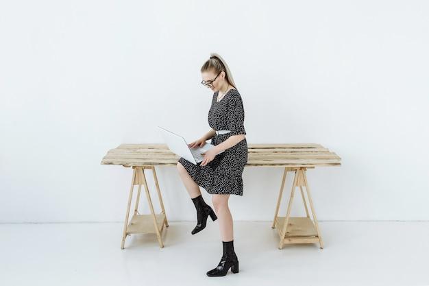Młoda uśmiechnięta kobieta w okularach freelancer siedzi przy stole i pracuje na laptopie przez internet
