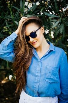 Młoda uśmiechnięta kobieta w okularach przeciwsłonecznych na zielonym tle naturalnych. portret kobiety na tle zielonych liści.