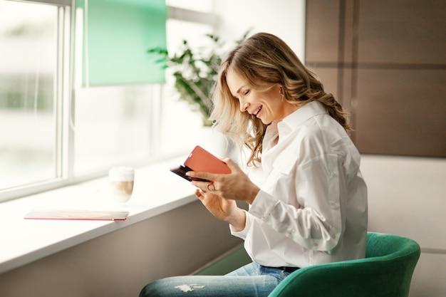Młoda uśmiechnięta kobieta w ubraniach biznesowych ogląda wideo w sieciach społecznościowych na smartfonie lub wysyła wiadomość tekstową do czytania podczas przerwy z filiżanką kawy w biurze firmy