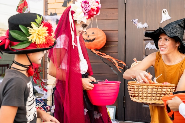 Młoda uśmiechnięta kobieta w żółtej sukience i czarnym kapeluszu czarownicy patrząc na uroczą wesołą dziewczynę halloween z koszem i dając jej słodycze
