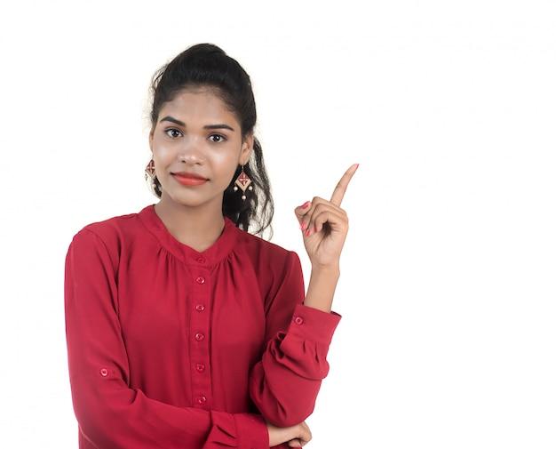 Młoda uśmiechnięta kobieta wskazuje palce kopiować przestrzeń na białej ścianie