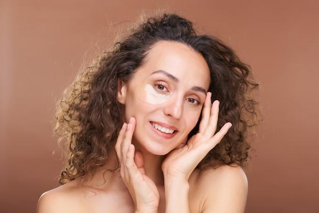 Młoda uśmiechnięta kobieta z ciemnymi kręconymi włosami i nawilżającymi plastrami pod oczami dotykającymi jej twarzy podczas zabiegu kosmetycznego w izolacji