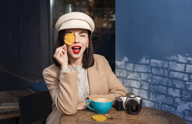 Młoda uśmiechnięta kobieta z jesień żółtymi liśćmi