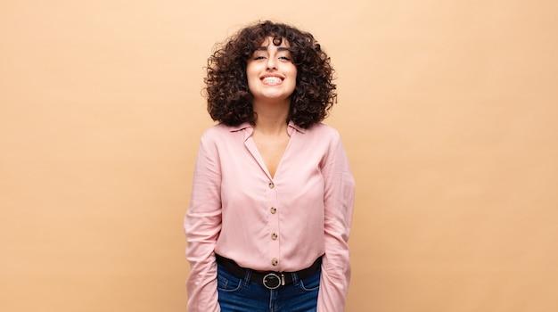 Młoda uśmiechnięta kobieta z kręconymi włosami i różową koszulą